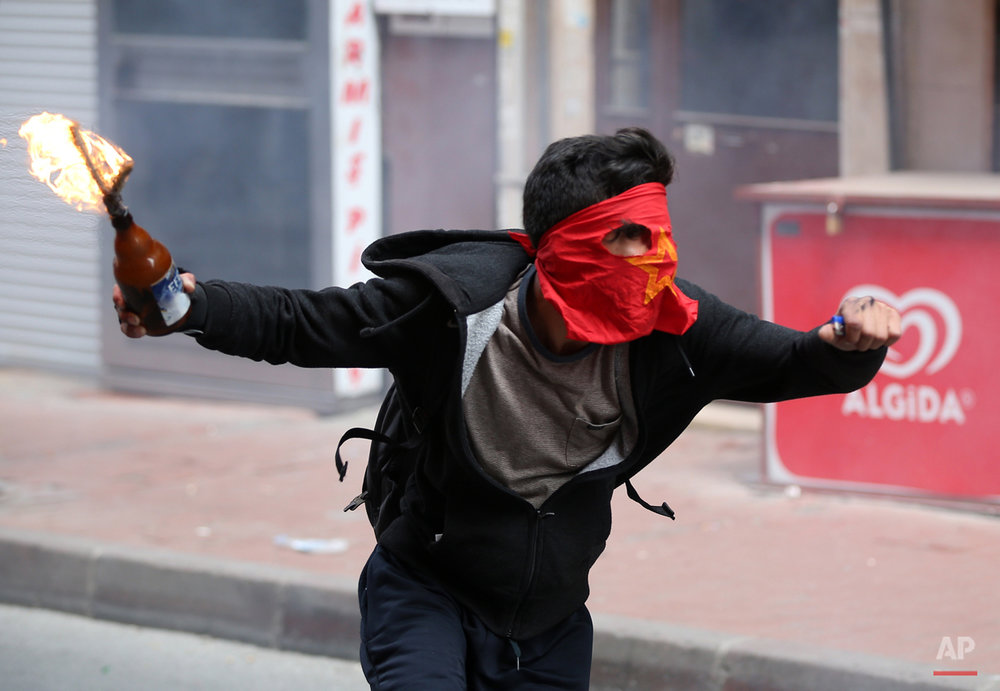 A demonstrator runs to hurl a firebomb towards riot police officers during clashes in Istanbul, Turkey, Friday, May 1, 2015.  Clashes erupted between police and May Day demonstrators in Istanbul on Friday as crowds determined to defy a government ban tried to march to the city's iconic Taksim Square.  Security forces pushed back demonstrators with a water cannon and tear gas. (AP Photo/Emrah Gurel)