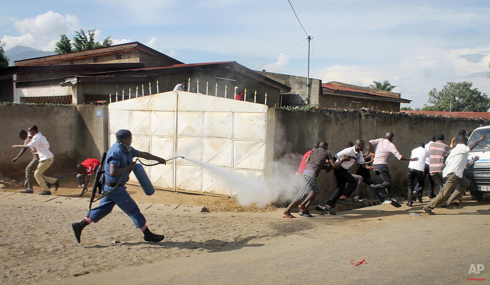 A Burundian riot policeman sprays tear gas on opposition protesters in the capital Bujumbura, Burundi Monday, April 27, 2015. Street protests continued Monday in Burundi as anger mounts over the ruling party's decision on Saturday to nominate President Pierre Nkurunziza for a third term. (AP Photo/Eloge Willy Kaneza)