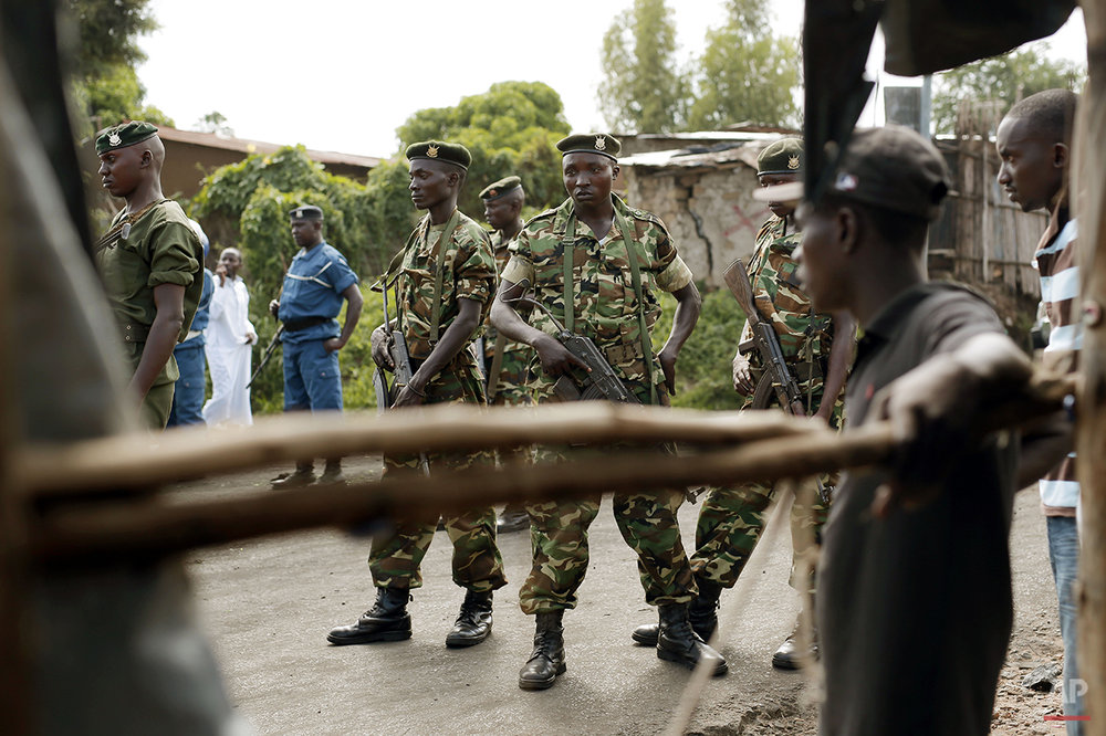 Burundi soldiers act as a buffer between demonstrator and police in Bujumbura, Burundi, Wednesday, April 29, 2015. Anti-government street demonstrations continued for a fourth day after six people died in protests against the move by President Pierre Nkurunziza to seek a third term. (AP Photo/Jerome Delay)