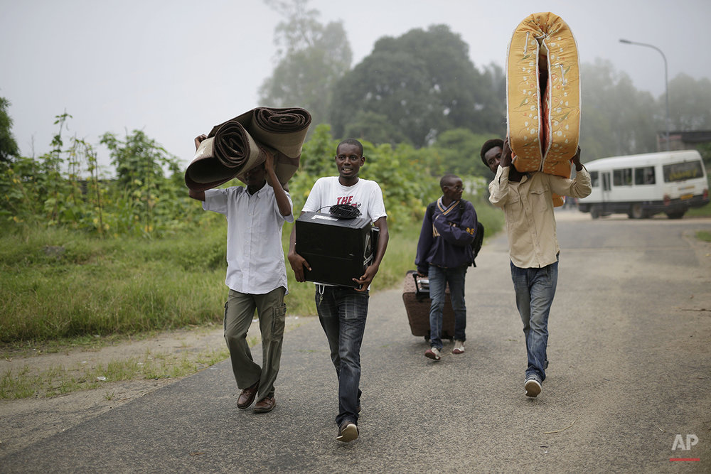 Students carry their belongings as they leave the Kiriki University campus in Bujumbura, Burundi Thursday, April 30, 2015, after the government issued and ordered for all campuses to close down. Bujumbura has been hit by street protests since Sunday as the security forces confront demonstrators who say a third term for President Pierre Nkurunziza would violate the country's constitution. (AP Photo/Jerome Delay)