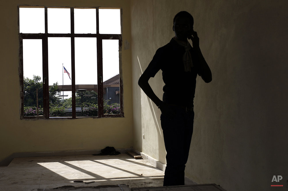 A student activist makes a phone call from a construction site adjacent to the US embassy, in Bujumbura, Burundi, Friday May 1, 2015. About 500 students spent the night outside the U.S. Embassy in Burundi's capital, asking the U.S. for protection as street protests went into their sixth day Friday against President Pierre Nkurunziza's decision to seek a third term. (AP Photo/Jerome Delay)
