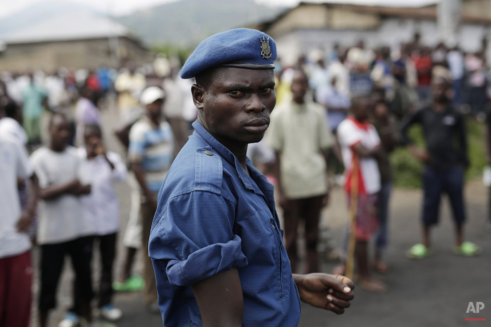 A Burundi police officer stands in front of a group of protesters in Bujumbura, Burundi, Wednesday, April 29, 2015. Anti-government street demonstrations continued for a fourth day after six people died in protests against the move by President Pierre Nkurunziza to seek a third term. (AP Photo/Jerome Delay)