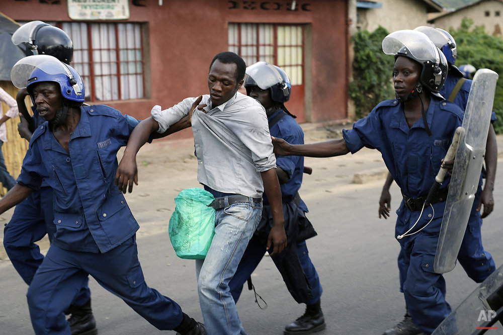 Burundi riot police detain a man suspected of throwing stones during clashes in the Musaga district of Bujumbura, Burundi, Tuesday April 28, 2015. Anti-government street demonstrations continued for a third day after six people died in protests against the move by President Pierre Nkurunziza to seek a third term. (AP Photo/Jerome Delay)