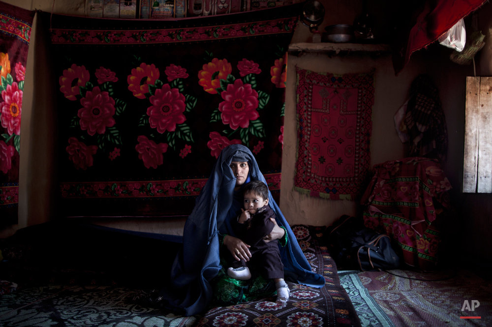 In this Sunday, March 30, 2014, photo, Afghan refugee, Wahida Nourallah, 26, a mother of 4 children, holds her son Atauallah, 2, while posing for a picture at her mud house on the outskirts of Islamabad, Pakistan. (Muhammed Muheisen/AP for Time Magazine)