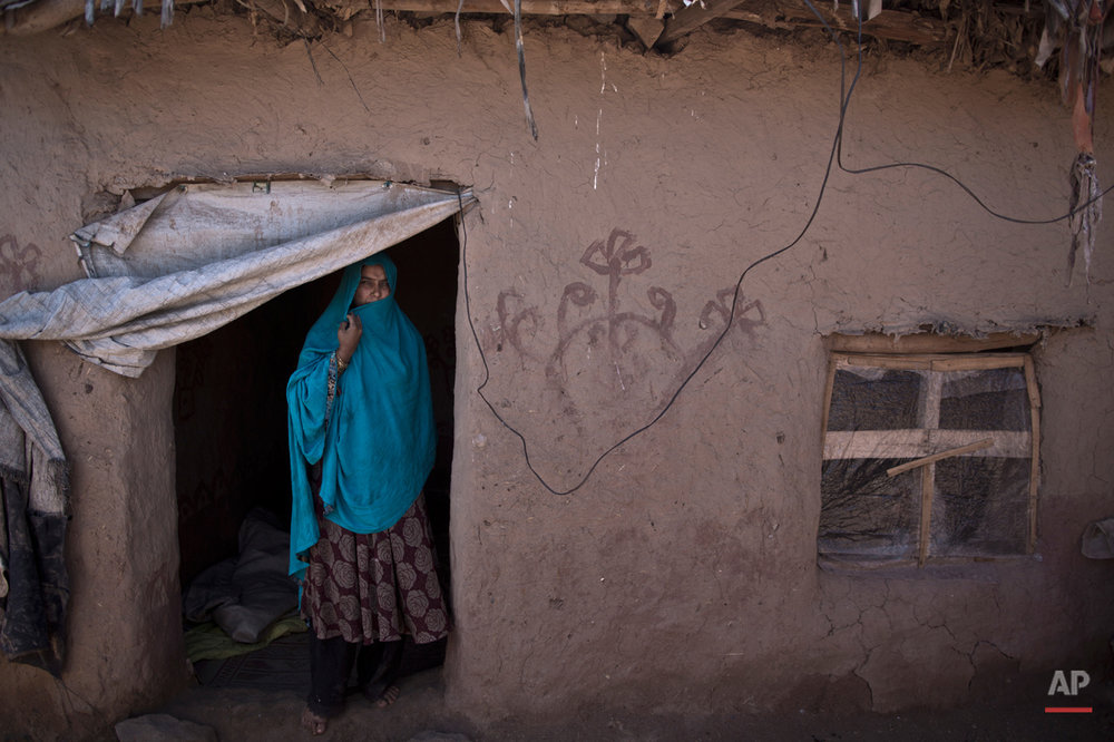In this Sunday, March 30, 2014, photo, Afghan refugee, Belquis Elias, 42, a mother of 4 adults, poses for a picture at the doorway of her mud home, on the outskirts of Islamabad, Pakistan.  (Muhammed Muheisen/AP for Time Magazine)