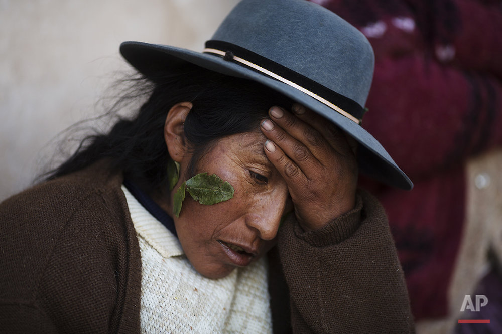 In this July 10, 2016 photo, Valeria Chuquibanca holds her head as she suffers a headache triggered by the heat reflected from the snow, one day after a heavy snow in San Antonio de Putina in the Puno region of Peru. Valeria said that sticking coca leaves near her eyes helps alleviate the pain. (AP Photo/Rodrigo Abd)