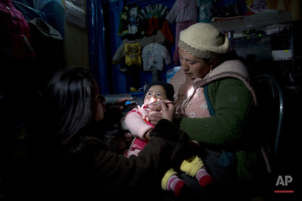 "In this July 11, 2016 photo, Ruth Aguilar holds her daughter Chaska, which translates as ""Star"" in the Quechua language, as a doctor inspects the baby suffering a respiratory infection in San Antonio de Putina in the Puno region of Peru. Two months into the cold season an estimated 14,000 children in the Andes have suffered from respiratory illnesses and 105 died, according to government figures. (AP Photo/Rodrigo Abd)"