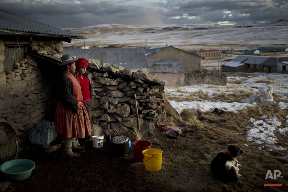 In this July 9, 2016 photo, Rosa Carcabusto and her daughter Maria Luque stand outside their home before cooking a dinner soup of wheat and dried potatoes, in San Antonio de Putina in the Puno region of Peru. Poverty has driven many farmers' children from their homes to work in illegal mines or Peru's flourishing cocaine trade. (AP Photo/Rodrigo Abd)