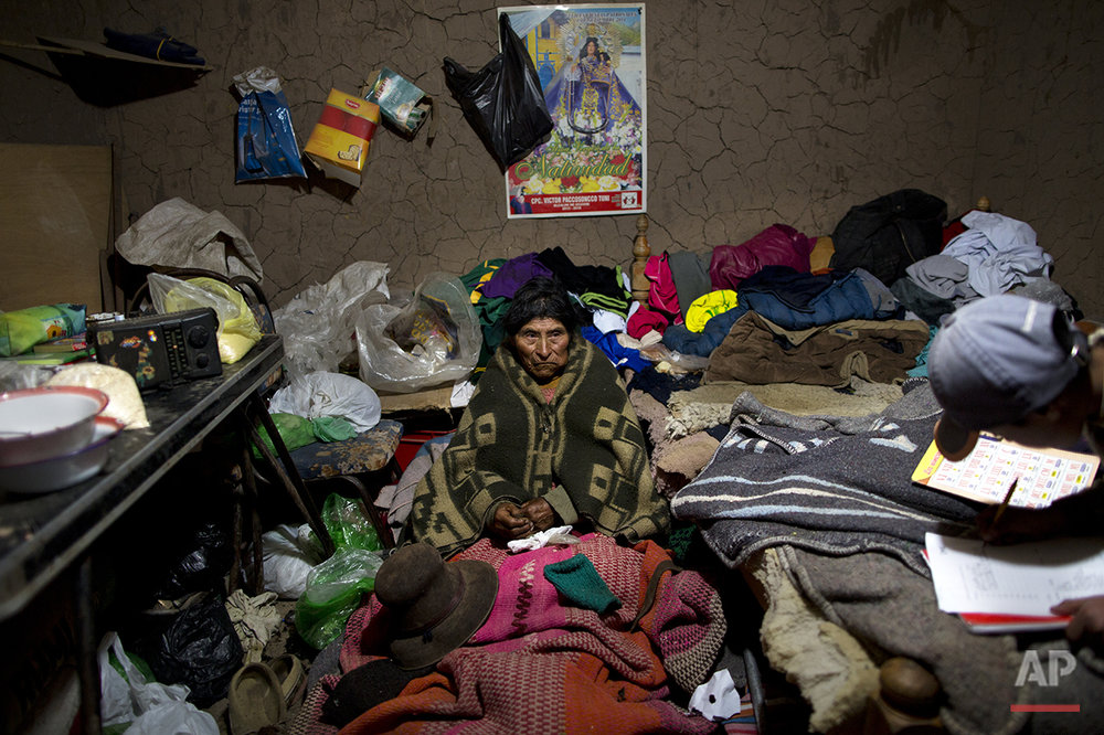 In this July 11, 2016 photo, Vicentina Javier rests inside a relative's adobe home as she recuperates from a respiratory illness in San Antonio de Putina in the Puno region of Peru. Authorities relocated Vicentina, 77, from her home to this village because she was in a even more sparsely populated area where there's no doctor nearby. (AP Photo/Rodrigo Abd)