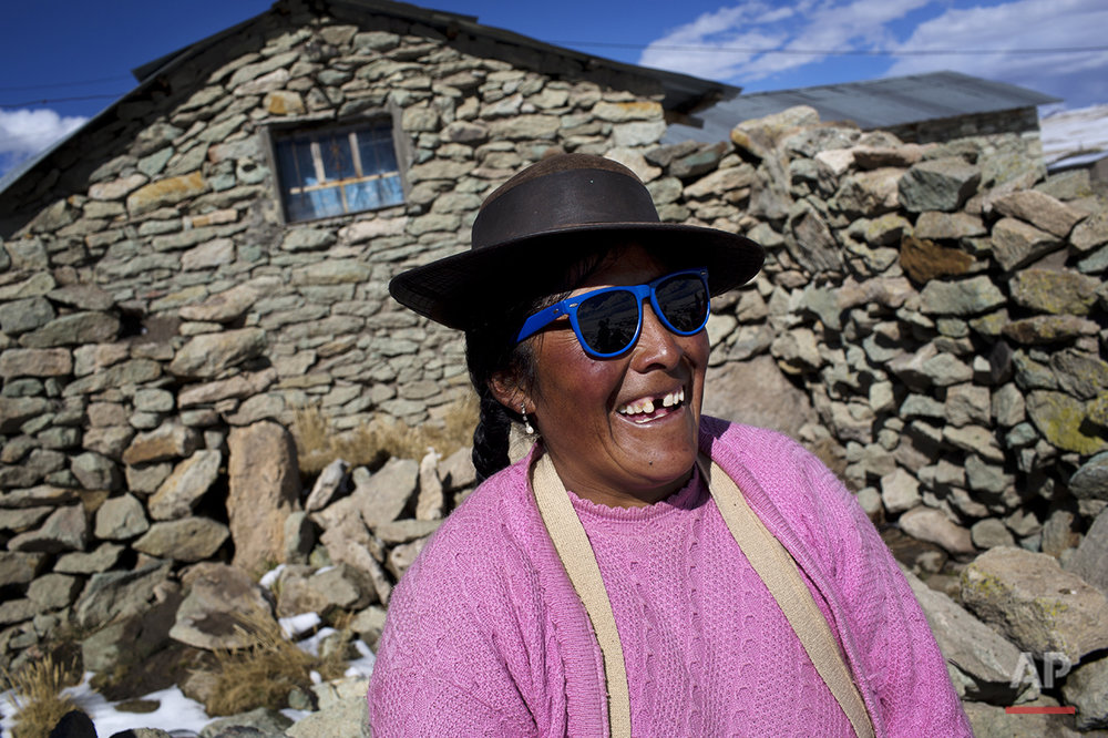 In this July 9, 2016 photo, Cecilia Callo Mamani laughs as her neighbors joke about her sunglasses in San Antonio de Putina in the Puno region of Peru. Mamani said she wears them to protect her eyes from the snow's strong reflection. (AP Photo/Rodrigo Abd)