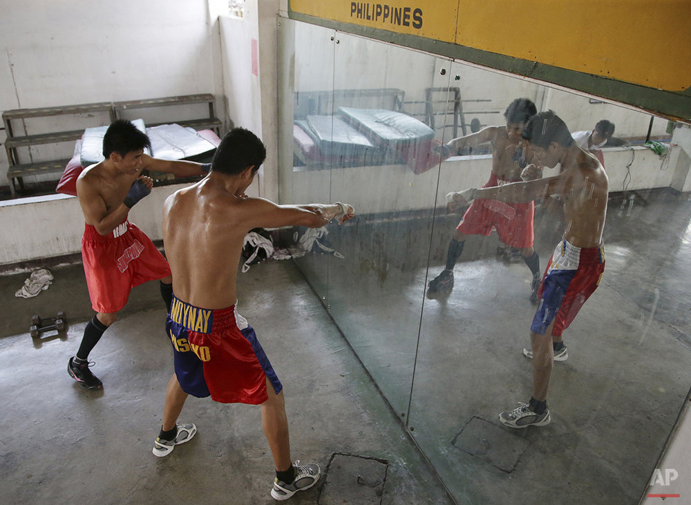 In this April 22, 2015, photo, Filipino boxer Rolly Macaso, left, and Joemarie Noynay practice in front of a mirror during their training at a boxing gym in suburban Paranaque, south of Manila, Philippines. Manny Pacquiao's rise from crushing poverty to global fame and fortune has inspired a whole generation of Filipino fighters, who look up to his legend as their dream and boxing as a ticket out of harsh lives and uncertainties. (AP Photo/Aaron Favila)