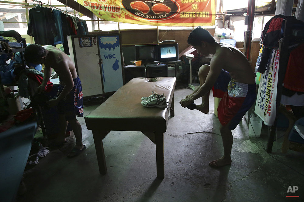 In this April 21, 2015, photo, Filipino boxer Meljun Penapin, right, removes his shoes at a dormitory where they stay during training in suburban Paranaque, south of Manila,  Philippines. Many young Filipinos aspire to become successful boxers in the country. The popularity of boxing has risen over the past years due to the record wins of eight division world champion and Filipino boxing icon Manny Pacquiao who is set to face undefeated Floyd Mayweather Jr. on May 2 in Las Vegas. (AP Photo/Aaron Favila)