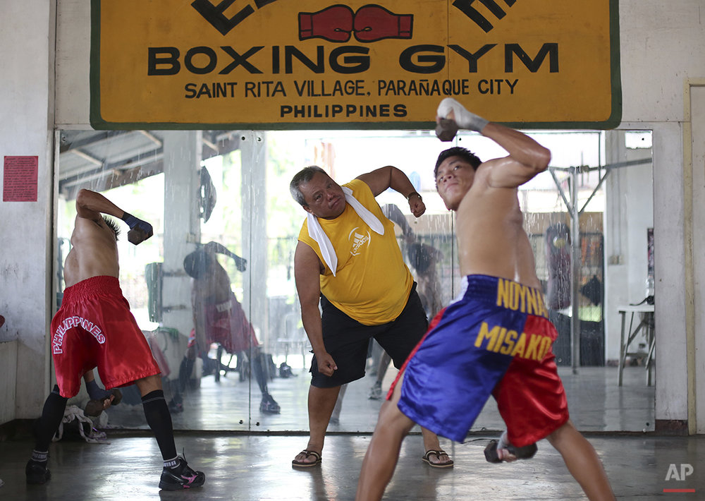 In this April 22, 2015, photo, Filipino boxing promoter and trainer Gabriel Elorde Jr., center, trains boxers at his boxing gym in suburban Paranaque, south of Manila, Philippines. Manny Pacquiao's rise from crushing poverty to global fame and fortune has inspired a whole generation of Filipino fighters, who look up to his legend as their dream and boxing as a ticket out of harsh lives and uncertainties. (AP Photo/Aaron Favila)
