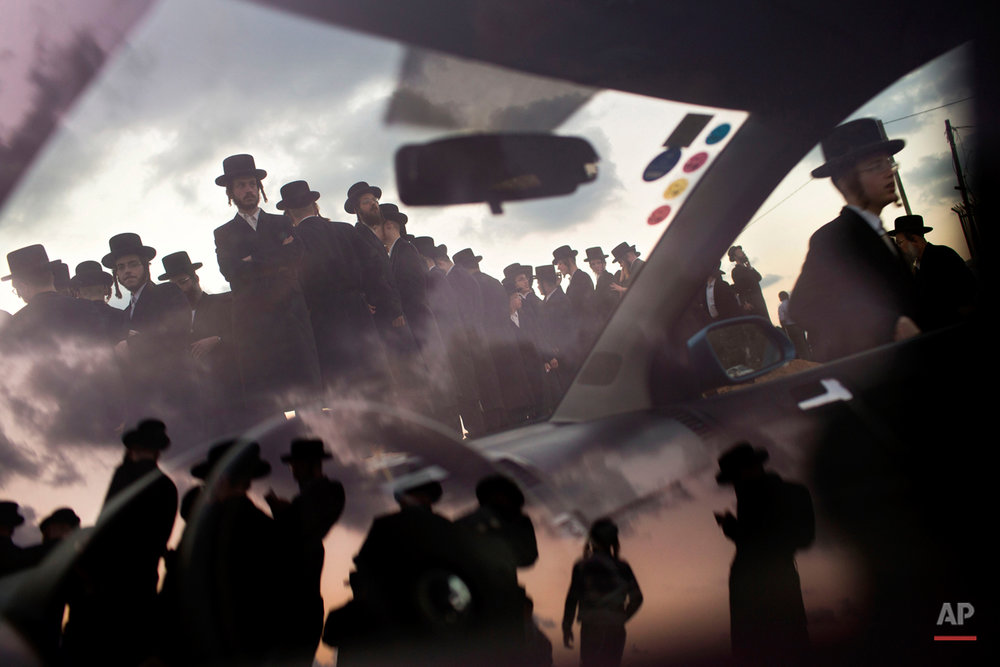 "Ultra-Orthodox Jews of the Hassidic sect Vizhnitz reflect on a car window as they gather on a hill overlooking the Mediterranean sea as they participate in a Tashlich ceremony in Herzeliya, Israel, Thursday, Oct. 2, 2014. Tashlich, which means ""to cast away"" in Hebrew, is the practice by which Jews go to a large flowing body of water and symbolically ""throw away"" their sins by throwing a piece of bread, or similar food, into the water before the Jewish holiday of Yom Kippur. (AP Photo/Oded Balilty)"