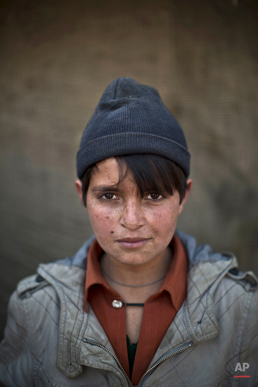 In this Saturday, Jan. 25, 2014 photo, Afghan refugee boy, Abdulrahman Bahadir, 13, poses for a picture, in a slum on the outskirts of Islamabad, Pakistan. (AP Photo/Muhammed Muheisen)