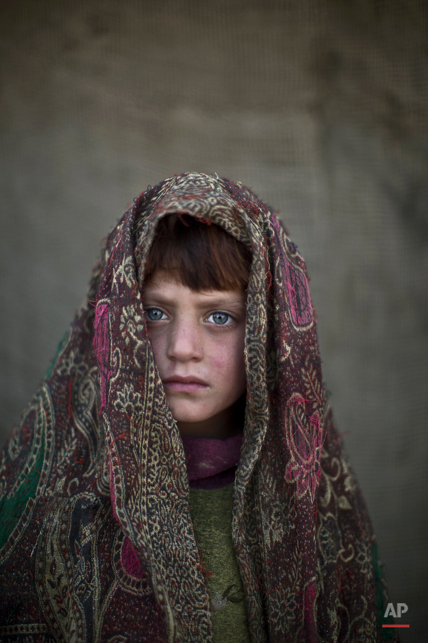 In this Friday, Jan. 24, 2014 photo, Afghan refugee girl, Naseebah Zarghoul, 6, poses for a picture, while playing with other children in a slum on the outskirts of Islamabad, Pakistan. (AP Photo/Muhammed Muheisen)