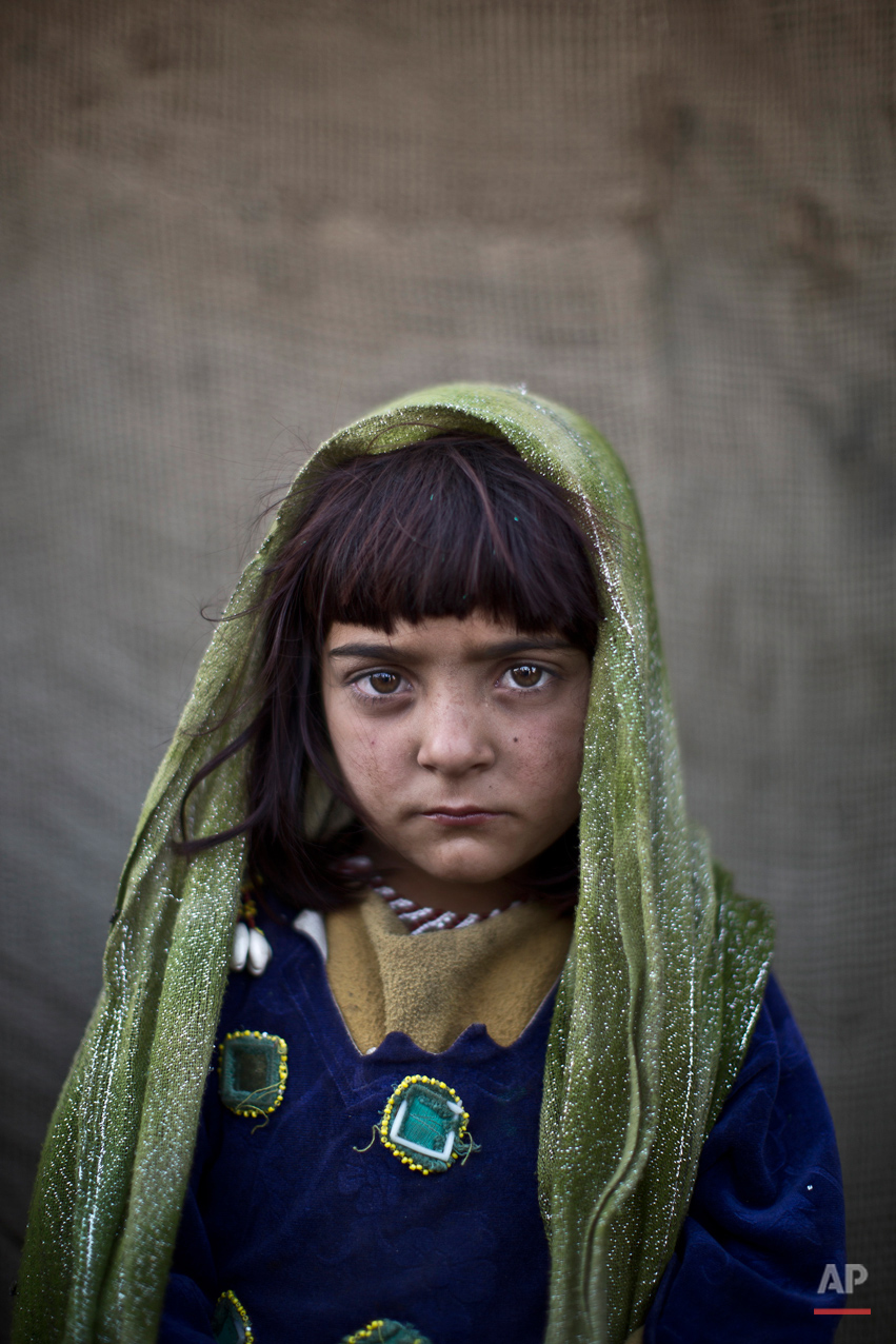 In this Saturday, Jan. 25, 2014 photo, Afghan refugee girl, Zarlakhta Nawab, 6, poses for a picture, while playing with other children in a slum on the outskirts of Islamabad, Pakistan. (AP Photo/Muhammed Muheisen)