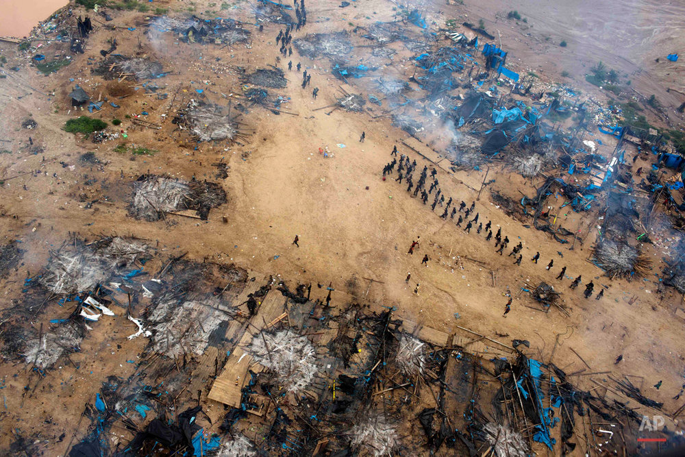 In this Nov. 12, 2014 photo, a column of policemen occupy a gold mining camp as part of an operation to eradicate illegal mining in the area  known as La Pampa, in Peru's Madre de Dios region. Peru's anti-illegal mining czar, retired army Gen. Augusto Soto, marched the men to the wasteland known as La Pampa, where 50,000 hectares of rainforest have been obliterated in the past six years. (AP Photo/Rodrigo Abd)