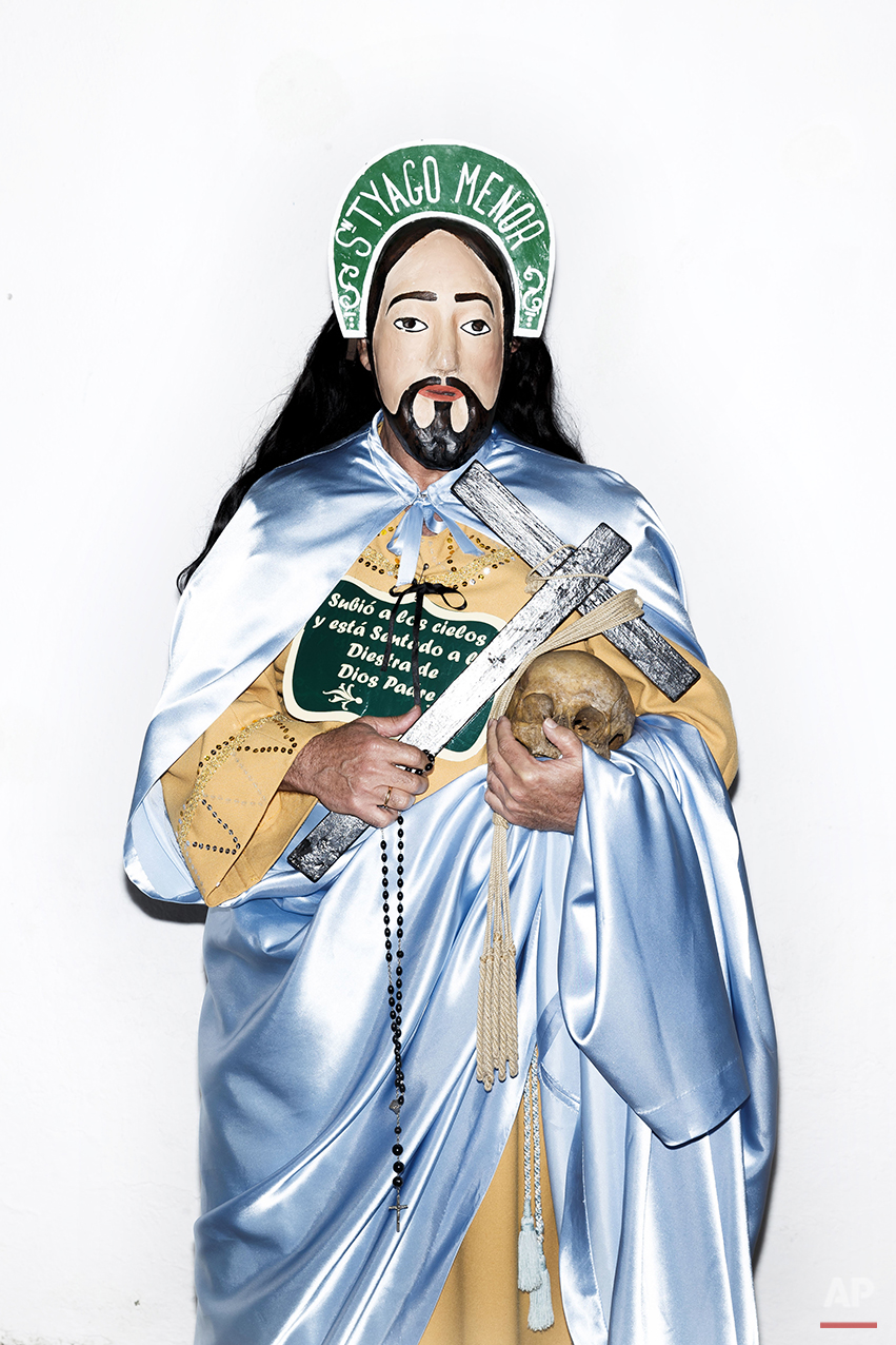 "A penitent poses for a picture dressed with typical Apostle dress, holding a Cross in one hand and an ancient human skull from a unidentified person, before the Holy Week procession by the 'Nuestro Padre Jesus Nazareno and Nuestra Señora de la Piedad' brotherhood in Iznajar, Spain, Friday, April 3, 2015. Among the characters taking part in the procession are the ""Brotherhood of the Apostles,"" represented, as the name suggests, by 12 townsfolk who don a distinctive mask, dress up in robes, carry a rosary and process behind an urn carved in the shape of the ""Dead Christ."" Each apostle carries a human skull, a black cross and words taken from the Roman Catholic credo. (AP Photo/Daniel Ochoa de Olza)"