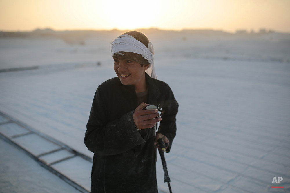 In this Wednesday, March 18, 2015 photo, a young worker smiles during a tea break at sunrise in the desert of Minya, southern Egypt. Some children as young as 10 years old work in the quarries to help their families, risking injury and sometimes death. (AP Photo/Mosa'ab Elshamy)