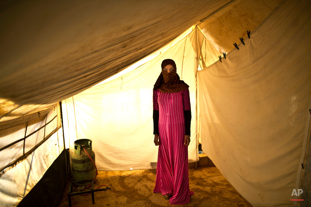 In this Monday, March 16, 2015 photo, Syrian refugee Samira Helal, 17, who is two months pregnant, poses for a portrait at  inside her tent at an informal tented settlement near the Syrian border, on the outskirts of Mafraq, Jordan. Nearly 3.8 million Syrians have fled their country and are now registered as refugees, according to the U.N. Most face increasingly desperate circumstances. (AP Photo/Muhammed Muheisen)