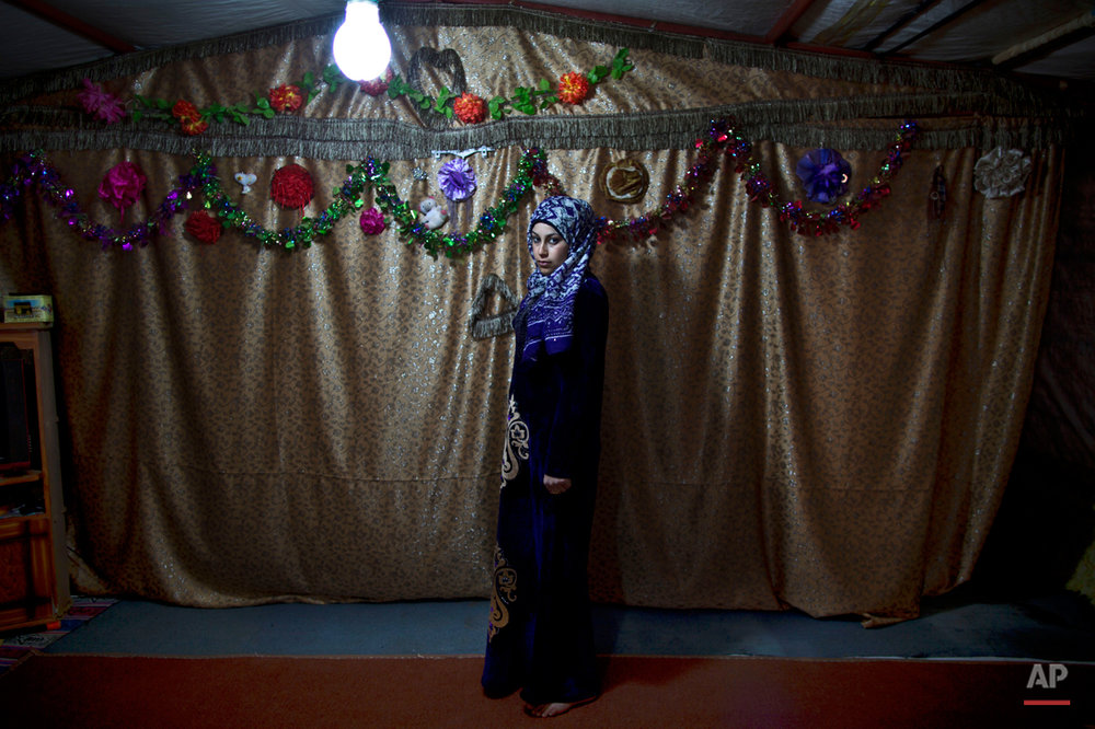 In this Tuesday, March 17, 2015 photo, pregnant Syrian refugee Huda Alsayil, 20, poses for a portrait inside her tent at an informal tented settlement near the Syrian border, on the outskirts of Mafraq, Jordan. ìA couple of weeks ago, I couldnít feel my baby moving in my belly so I panicked and didnít know what to do since I canít afford heading to a clinic and check,î says Alsayil, who fled fighting in Hama three years ago and is five months pregnant. (AP Photo/Muhammed Muheisen)