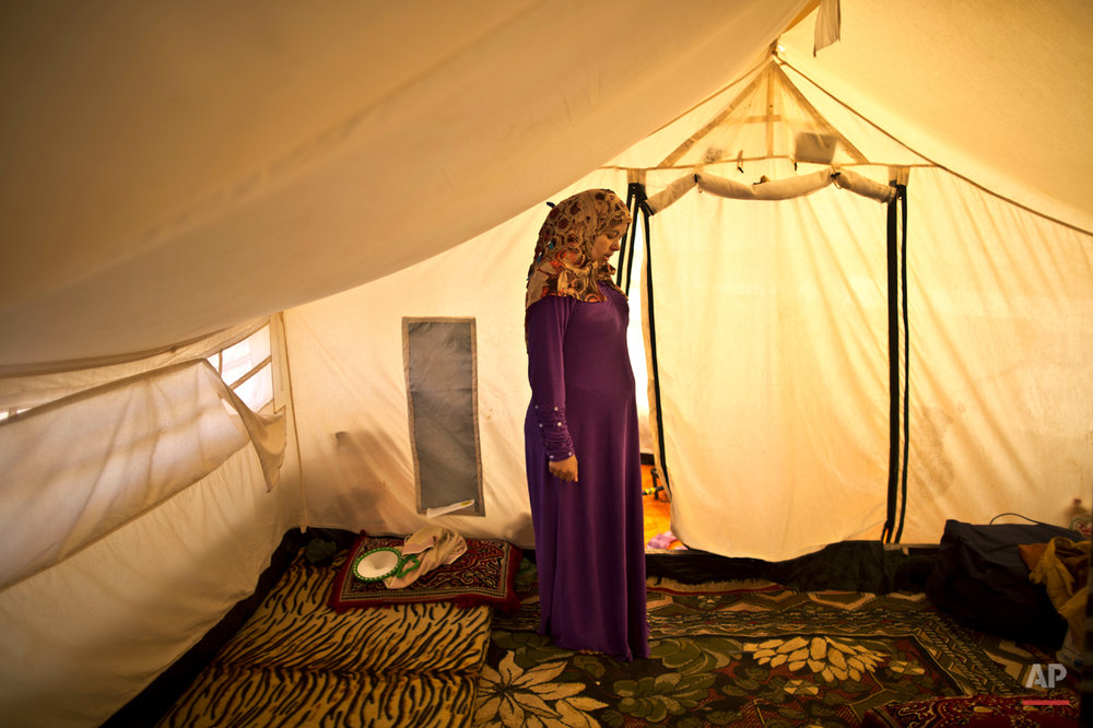 In this Tuesday, March 17, 2015 photo, Syrian refugee Adala Ismail, 32, who is six months pregnant, poses for a portrait inside her tent at an informal settlement near the Syrian border, on the outskirts of Mafraq, Jordan. Expectant mothers in these settlements often canít afford doctor visits and face potential health hazards because of lack of running water and other challenges. By contrast, pregnant women in Jordanís three recognized refugee camps have access to free services, including pre-natal care and delivery, according to the U.N. refugee agency. (AP Photo/Muhammed Muheisen)