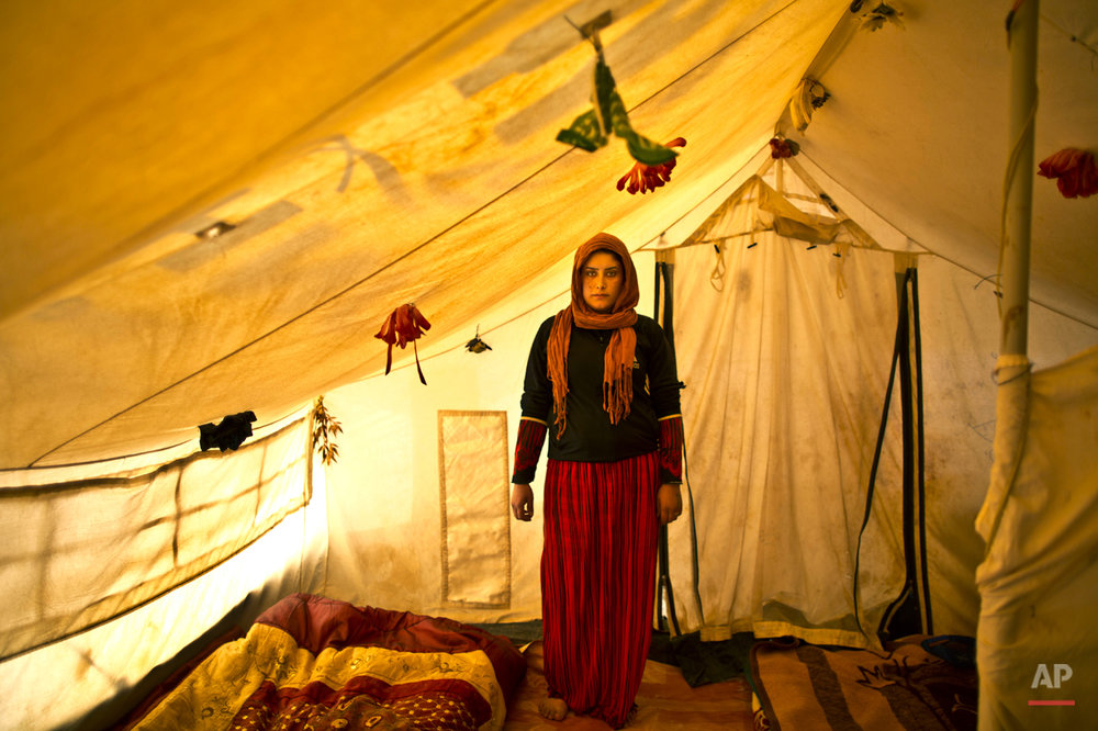 In this Monday, March 16, 2015 photo, pregnant Syrian refugee Wadhah Hamada, 22, poses for a portrait inside her tent at an informal settlement near the Syrian border, on the outskirts of Mafraq, Jordan. Hamada, who fled al-Hasaka, Syria, says she has no clue how her four-month pregnancy is progressing. ìI canít afford to pay 50 Jordanian dinars ($70) for my ultrasound and other medical checks,î she says. ìOur future is dark, my life is in a tent and my first childís life won't be different.î (AP Photo/Muhammed Muheisen)