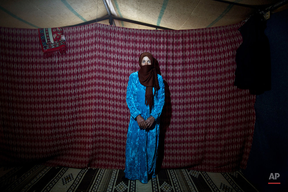 In this Monday, March 16, 2015 photo, Syrian refugee Thuraya Nayif, 40, a mother of seven children in her second month of pregnancy, poses for a photograph inside her tent at an informal settlement near the Syrian border, on the outskirts of Mafraq, Jordan. Pregnant refugee women living in informal tent settlements are among the most vulnerable of the hundreds of thousands of Syrians who have found shelter in Jordan. They often canít afford doctor visits and face potential health hazards because of lack of running water and other challenges. (AP Photo/Muhammed Muheisen)