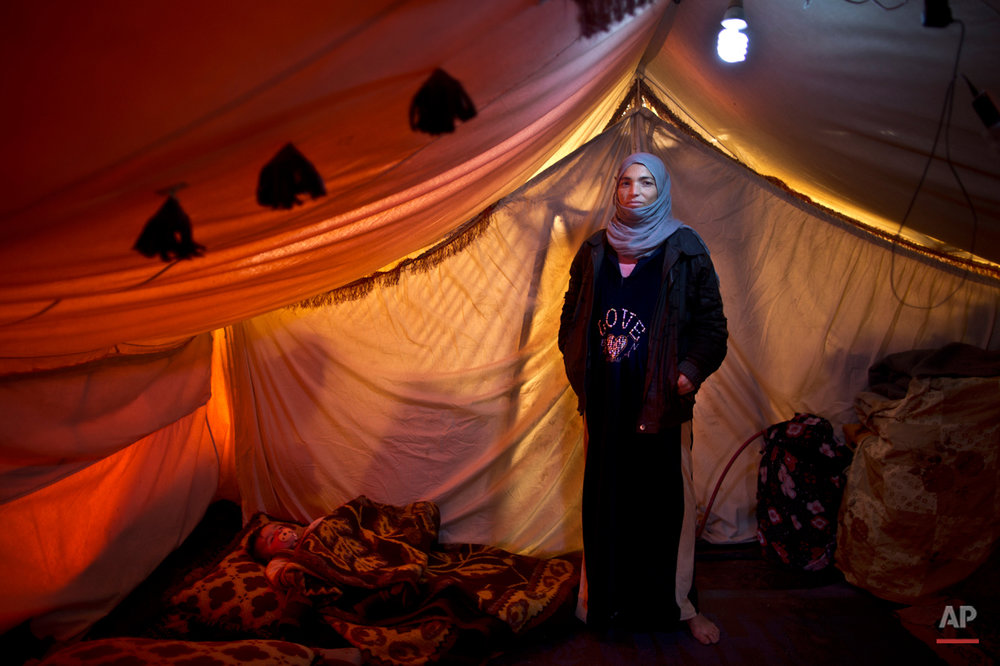 In this Monday, March 16, 2015 photo, Syrian refugee Wazeera Elaiwi, 29, a mother of two children now six months pregnant, poses for a portrait inside her tent at an informal settlement near the Syrian border, on the outskirts of Mafraq, Jordan. Pregnant refugee women living in informal tent settlements are among the most vulnerable of the hundreds of thousands of Syrians who have found shelter in Jordan. (AP Photo/Muhammed Muheisen)