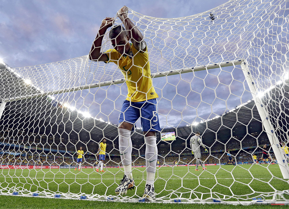 In this July 8, 2014, photo, Brazil's Fernandinho reacts after Germany's Toni Kroosduring scored his side's third goal during the World Cup semifinal soccer match between Brazil and Germany at the Mineirao Stadium in Belo Horizonte, Brazil. (AP Photo/Natacha Pisarenko)