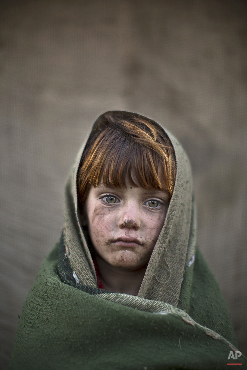 In this Friday, Jan. 24, 2014 photo, Afghan refugee girl, laiba Hazrat, 6, poses for a picture, while playing with other children in a slum on the outskirts of Islamabad, Pakistan. For more than three decades, Pakistan has been home to one of the world's largest refugee communities: hundreds of thousands of Afghans who have fled the repeated wars and fighting their country has undergone. Since the 2002 U.S.-led invasion of Afghanistan, some 3.8 million Afghans have returned to their home country, according to the U.N.'s refugee agency. (AP Photo/Muhammed Muheisen)