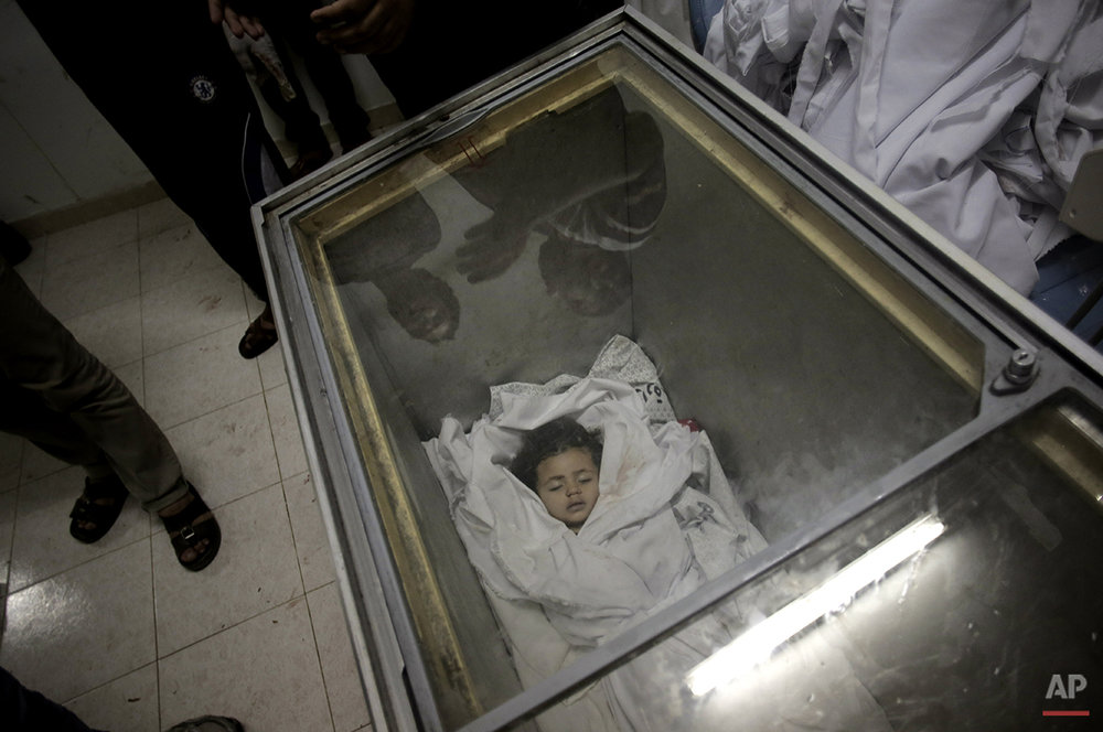 Palestinians gather around the lifeless body of Raghad Masoud, 34 months, who was killed in an Israeli strike, after she was laid in a freezer as the hospital morgue was full at Rafah refugee camp, in southern Gaza Strip, Monday, Aug. 4, 2014.  Israel withdrew most of its ground troops from the Gaza Strip on Sunday in an apparent winding down of the nearly monthlong operation against Hamas that has left more than 1,800 Palestinians and more than 60 Israelis dead.  (AP Photo/Khalil Hamra)