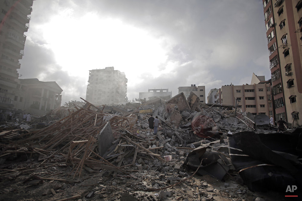 Palestinians inspect the rubble of the Al-Zafer apartment tower following Israeli airstrikes Saturday that collapsed the 12-story building, in Gaza City, Sunday, Aug. 24, 2014. The Israeli army said the Gaza City apartment tower was targeted because a Hamas command center operated from there. The weekend strikes by Israel marked the first time large buildings were toppled signaling a new escalation in seven weeks of fighting with Hamas. (AP Photo/Khalil Hamra)