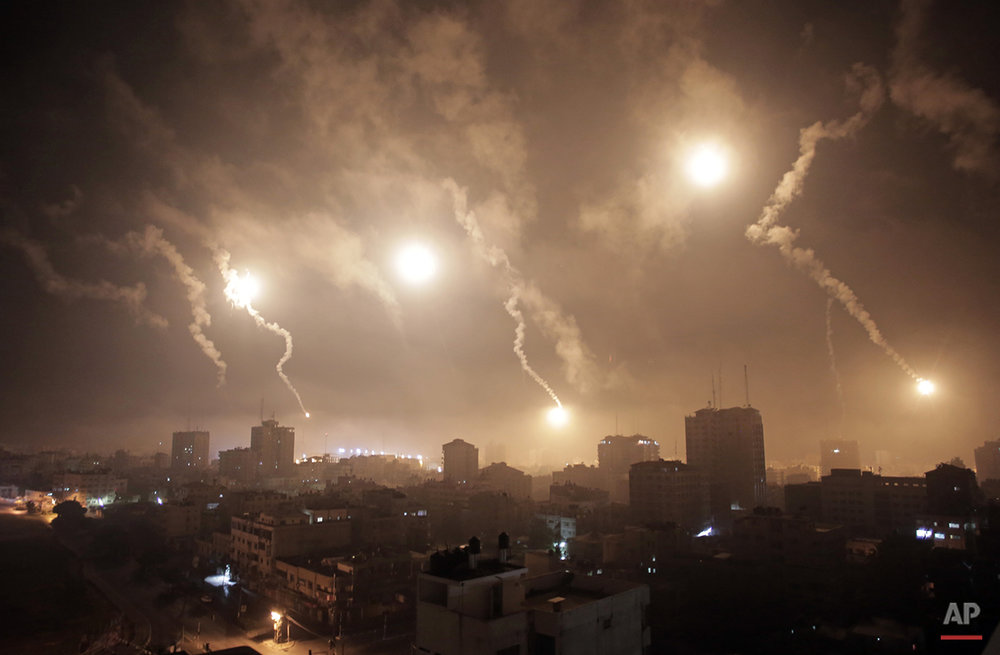 Israeli forces' flares light up the night sky of Gaza City on early Tuesday, July 29, 2014. A truce between Israel and Hamas militants in Gaza remained elusive as diplomats sought to end the fighting at the start of the Eid al-Fitr holiday, marking the end of the Muslim holy month of Ramadan. (AP Photo/Khalil Hamra)