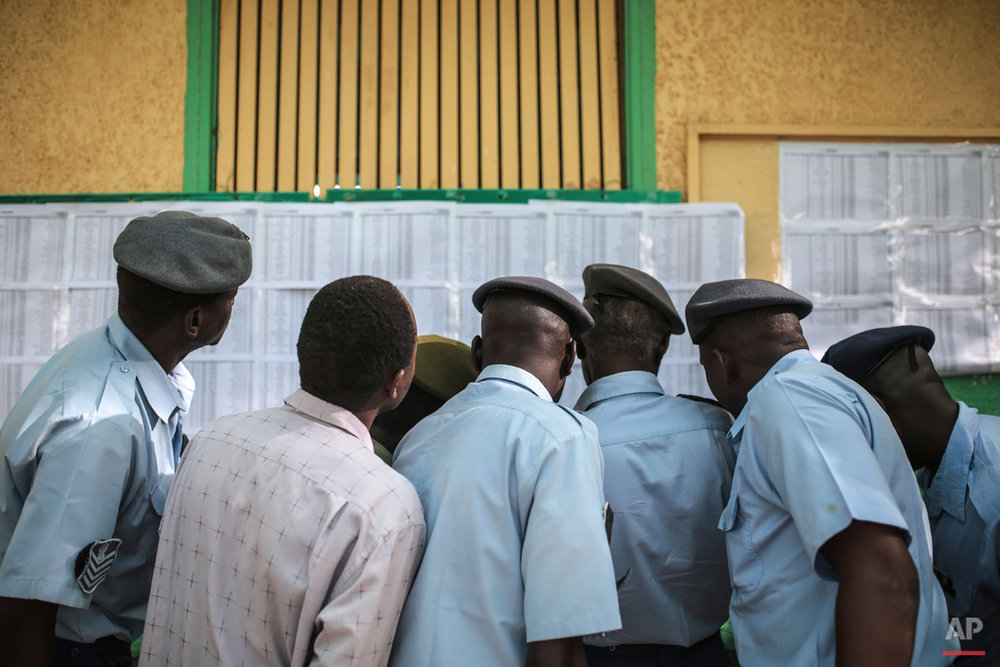 Members of the Sudanese security forces look for their names on a voters list outside a polling station where they are due to vote, on the first day of Sudan's presidential and legislative elections, in Khartoum, Sudan, Monday, April 13, 2015. (AP Photo/Mosa'ab Elshamy)
