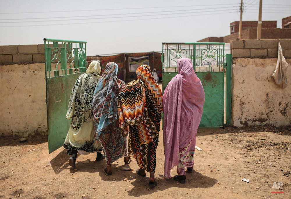 Sudanese women leave after voting at a polling station, on the first day of Sudan's presidential and legislative elections, in Izba, an impoverished neighborhood on the outskirts of Khartoum, Sudan, Monday, April 13, 2015. (AP Photo/Mosa'ab Elshamy)