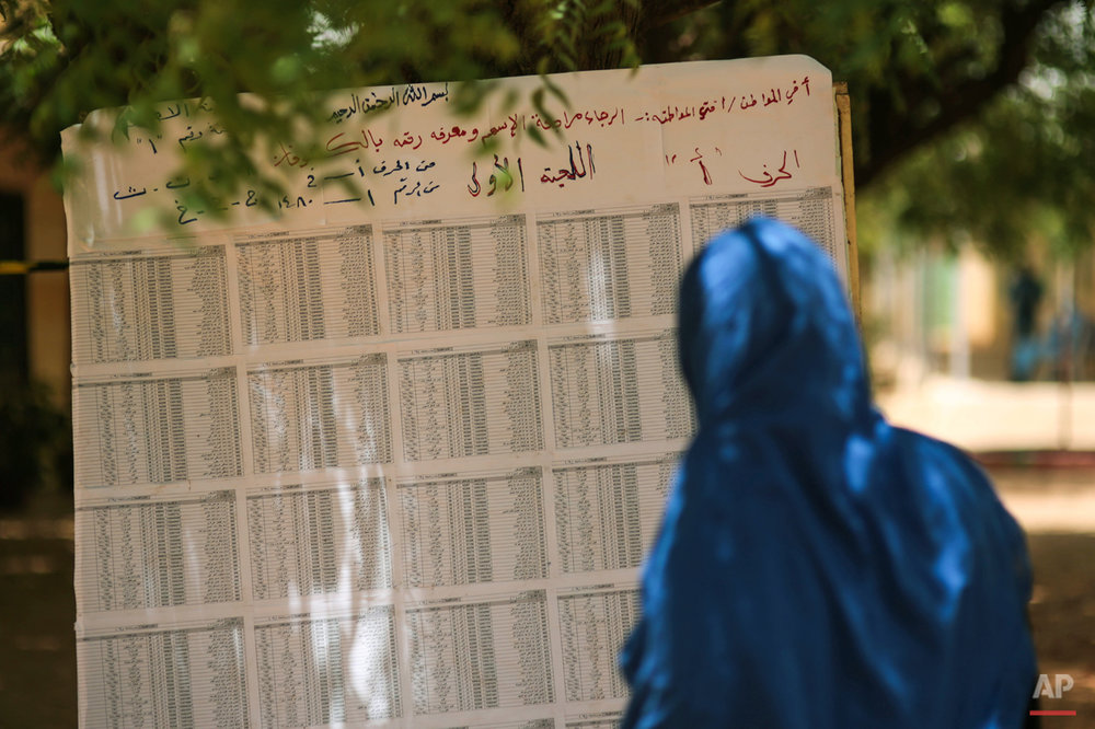 A Sudanese woman looks for her name on a voters list outside a polling station where she is due to to vote, on the first day of Sudan's presidential and legislative elections, in Izba, an impoverished neighborhood on the outskirts of Khartoum, Sudan, Monday, April 13, 2015. (AP Photo/Mosa'ab Elshamy)