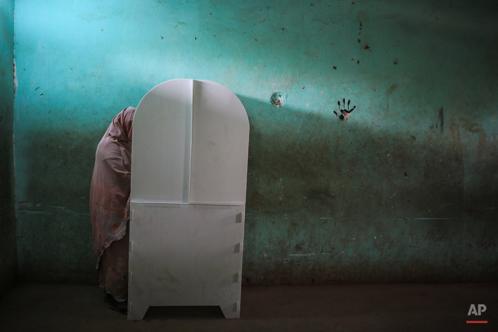 A Sudanese woman fills her ballot before voting at a polling station, on the first day of Sudan's presidential and legislative elections, in Izba, an impoverished neighborhood on the outskirts of Khartoum, Sudan, Monday, April 13, 2015. (AP Photo/Mosa'ab Elshamy)
