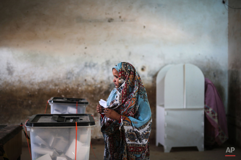 A Sudanese woman pauses before casting her ballot at a polling station, on the first day of Sudan's presidential and legislative elections, in Izba, an impoverished neighborhood on the outskirts of Khartoum, Sudan, Monday, April 13, 2015. (AP Photo/Mosa'ab Elshamy)