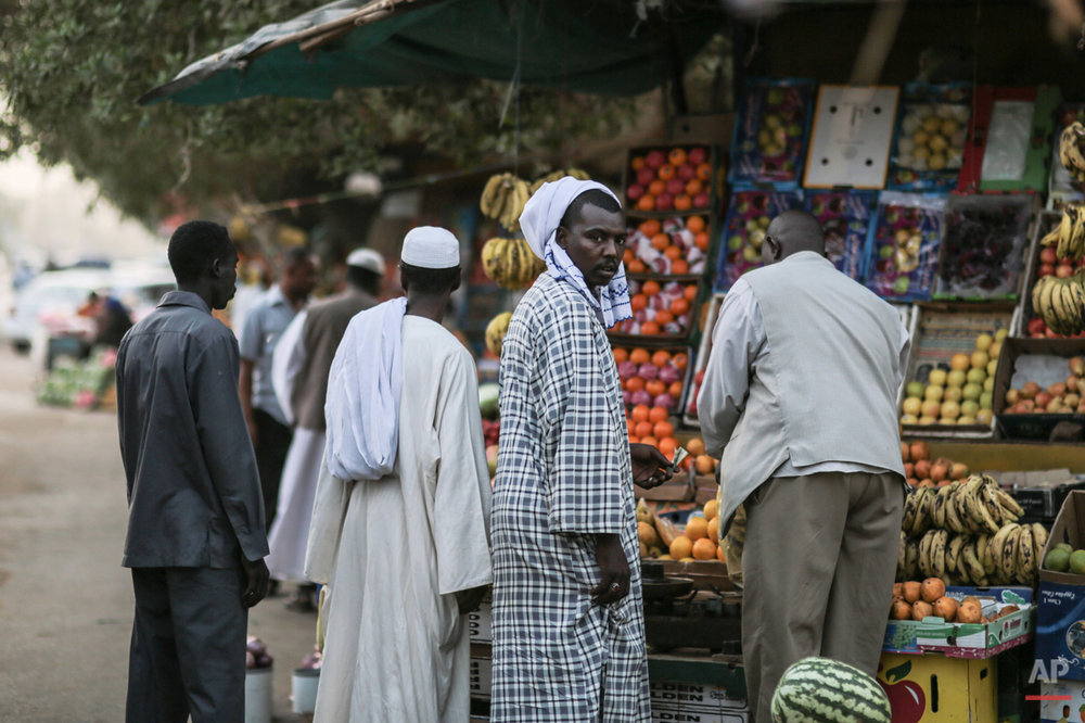 In this Saturday, April 11, 2015 photo, men shop for fruit in Omdurman, Sudan. Nearly 13 million people are registered to vote for president and the 450-member legislative council starting Monday. Some 11,000 polling centers will be open through Wednesday, and results are expected on April 27. (AP Photo/Mosa'ab Elshamy)