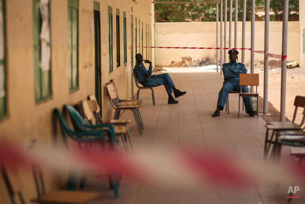 Sudanese security forces sit outside a polling station, on the first day of Sudan's presidential and legislative elections, in Izba, an impoverished neighborhood on the outskirts of Khartoum, Sudan, Monday, April 13, 2015. (AP Photo/Mosa'ab Elshamy)