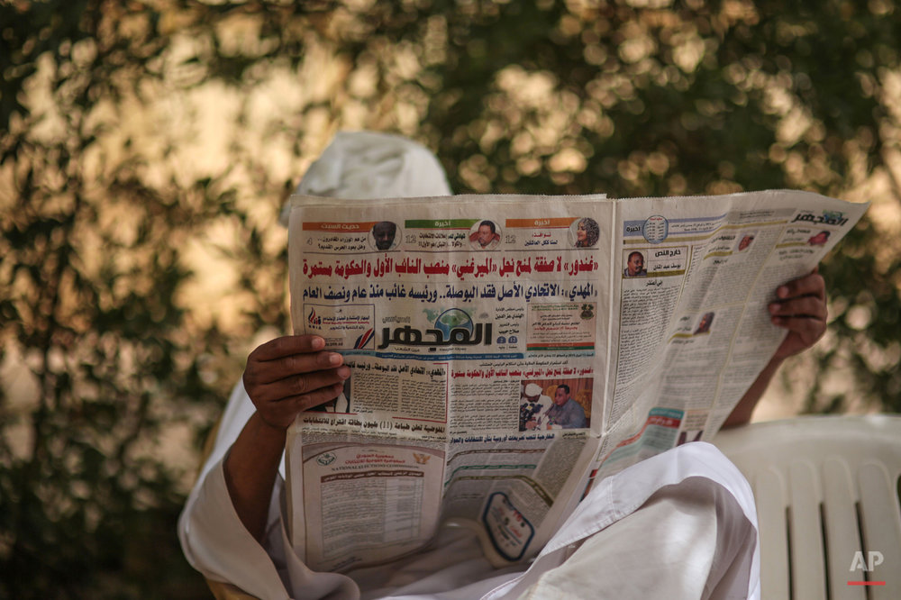 In this Saturday, April 11, 2015 photo, a man reads a newspaper during a sit-in organized by Sudanese opposition parties at the headquarters of Umma, one of Sudanís biggest opposition parties, in Khartoum, Sudan, to denounce the upcoming presidential elections where longtime autocratic President Omar al-Bashir is expected to secure easy victory. (AP Photo/Mosa'ab Elshamy)