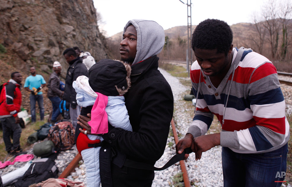 In this Saturday, Feb. 28, 2015 photo Jean-Paul Apetey of Ivory Coast receives help from Francis Tchiaze of Cameroon as he helps to carry ten-months-old Christian on their way to the town of Evzonoi, Greece.  The tide of hopeful migrants pours through the vulnerable 'back-door' countries in the hope of entering the 28-nation European Union, and although most people don't make it, the human tide continues to grow, according to Frontex, the EU agency that helps governments police the blocís leaky frontiers. (AP Photo/Dalton Bennett)