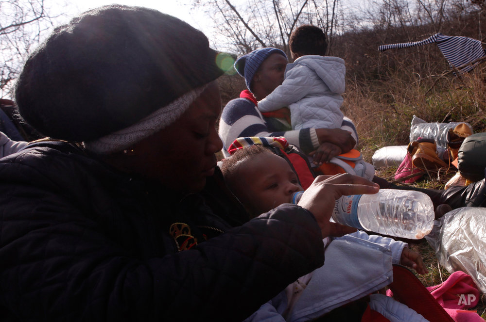 In this Saturday, Feb. 28, 2015 photo a migrant from Cameroon feeds 10-months-old Kendra Koffi on their way to the Greek-Macedonian border near the town of Polikastro, Greece.  The tide of hopeful migrants pours through the vulnerable 'back-door' countries in the hope of entering the 28-nation European Union, and although most people don't make it, the human tide continues to grow, according to Frontex, the EU agency that helps governments police the blocís leaky frontiers. (AP Photo/Dalton Bennett)