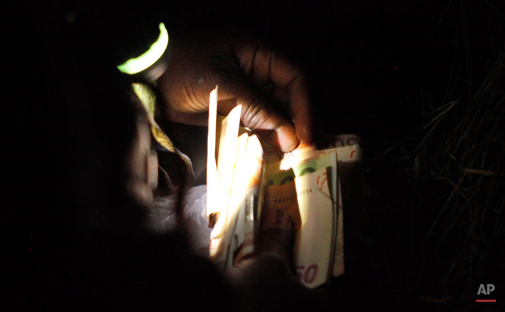In this Thursday, March 5, 2015 photo a woman holds a flashlight in her mouth as she counts her savings near Nogotino, Macedonia.  The tide of hopeful migrants pours through the vulnerable 'back-door' countries in the hope of entering the 28-nation European Union, and although most people don't make it, the human tide continues to grow, according to Frontex, the EU agency that helps governments police the blocís leaky frontiers. (AP Photo/Dalton Bennett)