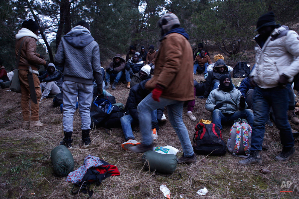 In this Monday, March 2, 2015 photo West African migrants prepare at dusk to march through the night near the town of Gevgelija, Macedonia, after crossing the border from Greece.  The tide of hopeful migrants pours through the vulnerable 'back-door' countries in the hope of entering the 28-nation European Union, and although most people don't make it, the human tide continues to grow, according to Frontex, the EU agency that helps governments police the blocís leaky frontiers. (AP Photo/Dalton Bennett)