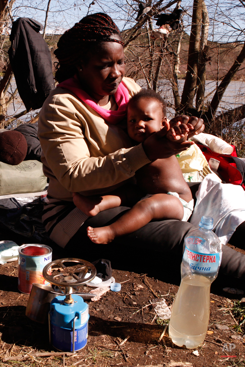 In this Tuesday, March 3, 2015 photo Sandrine Koffi washes her 10-months-old daughter Kendra with river water during a rest near the village of Marvintsi, Macedonia.  The tide of hopeful migrants pours through the vulnerable 'back-door' countries in the hope of entering the 28-nation European Union, and although most people don't make it, the human tide continues to grow, according to Frontex, the EU agency that helps governments police the blocís leaky frontiers. (AP Photo/Dalton Bennett)