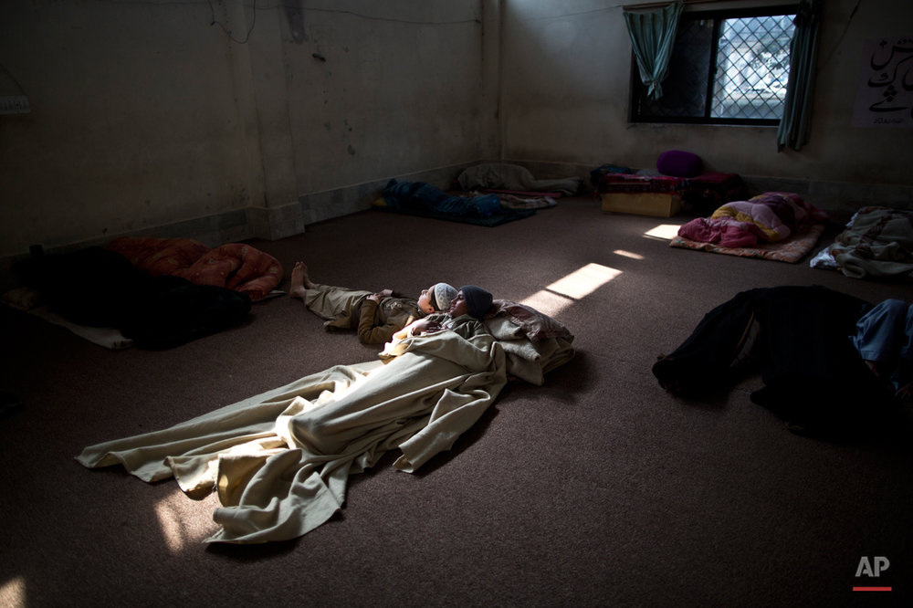 In this Saturday, Jan. 31, 2015 photo, Pakistani students of a madrassa, or Islamic school, sleep on the ground of their seminary in Islamabad, Pakistan. (AP Photo/Muhammed Muheisen)