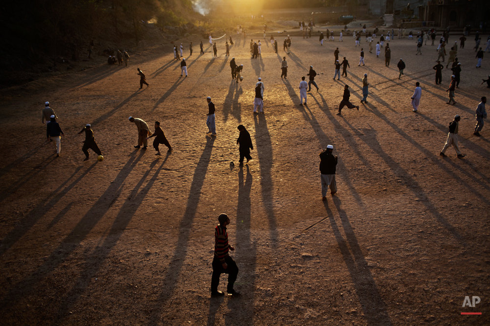 In this Tuesday, Jan. 27, 2015 photo, Pakistani students of a madrassa, or Islamic school, play football in their seminary's yard as the sun sets on the outskirts of Islamabad, Pakistan. Thereís no exact number of madrassas in Pakistan, but estimates put the number in the tens of thousands. They provide food, housing and a religious education to students from around the country. Many teach both male and female students. (AP Photo/Muhammed Muheisen)